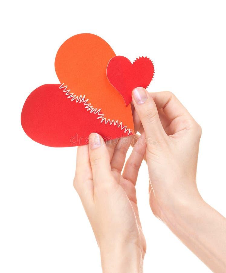 Corações quebrados grandes e pequenos nas mãos da mulher fotografia de stock royalty free