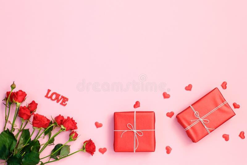 Corações, rosa e caixa de presente vermelhos no fundo cor-de-rosa fotos de stock