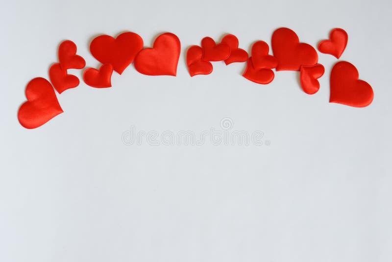 Corações vermelhos em um fundo branco na parte superior da imagem Espaço livre para cumprimentos do dia de Valentim e confissões  imagem de stock