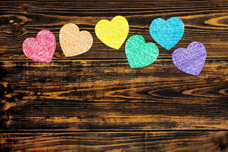 Cora??es pintados em cores de LGBT Localizado no fundo de madeira foto de stock royalty free