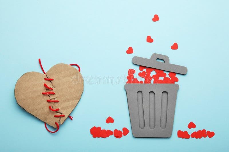 Cora??o e relacionamento rejeitados nos pares Cora??es quebrados vermelhos no balde do lixo foto de stock