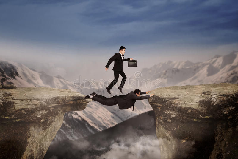 Coragem dos homens de negócios através do penhasco foto de stock