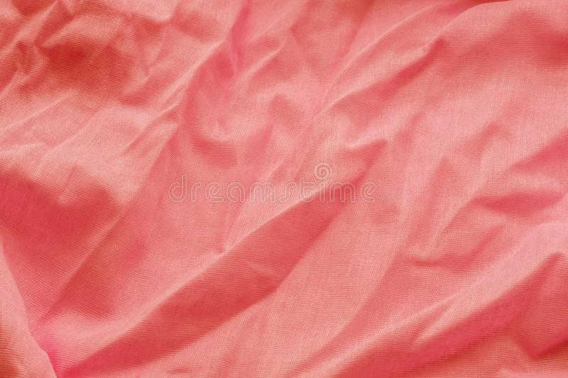 Coral background from a textile material with wicker pattern, closeup. Cloth backdrop. Crumpled fabric. Selective focus.  royalty free stock image
