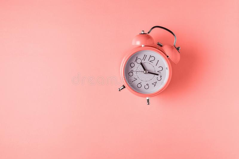 Coral color alarm clock on bright background. Minimal concept royalty free stock photography