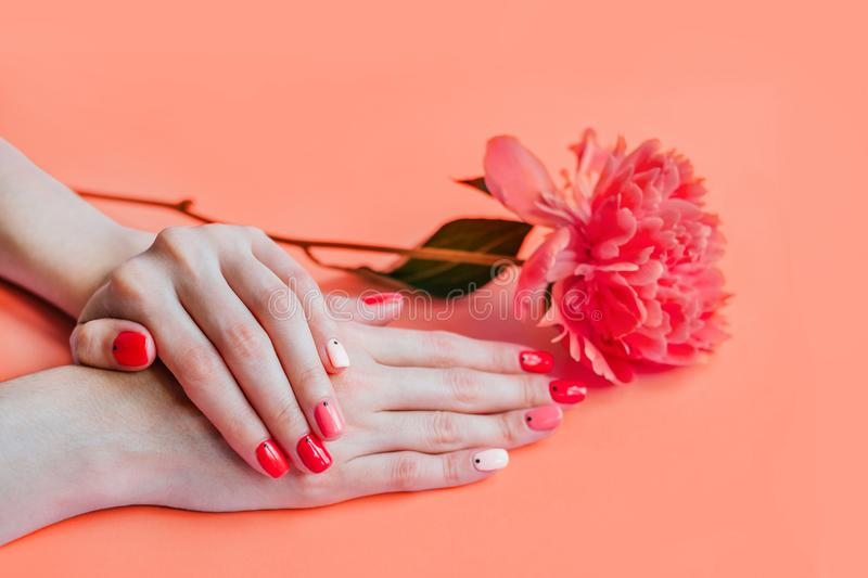 Coral summer manicure. Coral color creative bright trendy summer manicure with nails of different color. Female hands with art nail design on pink background and stock images