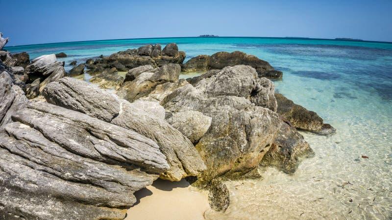 Coral de pedra na praia com o mar azul da água de turquesa e na areia no jawa do karimun imagens de stock