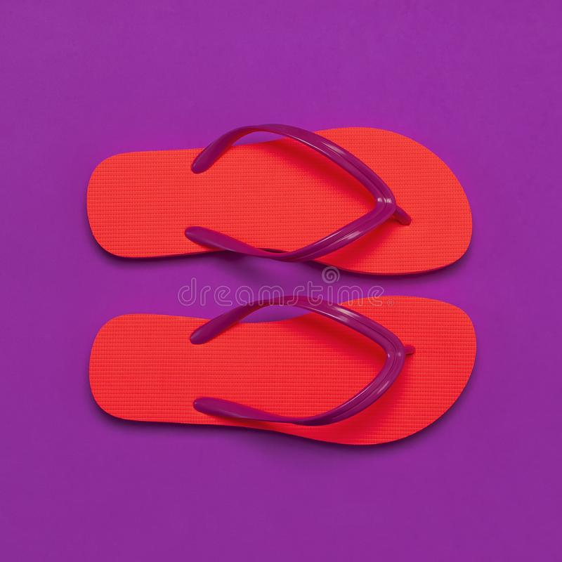 Coral flip flops on purple background. Flat lay, top view, copy space. Creative summer vacation travel background. Women`s summer royalty free stock photos