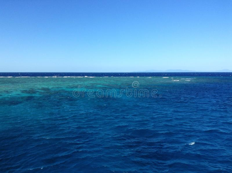 Coral reef in the great barrier reef, visible by coloration of the water, reefs are often bleached stock photos
