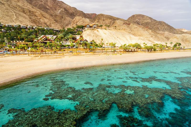 Coral reef of Red Sea, beach and desert near Eilat, Israel. Coral reef of Aqaba Bay in Red Sea, empty beach and desert near Eilat, Israel. Contrast between royalty free stock photo