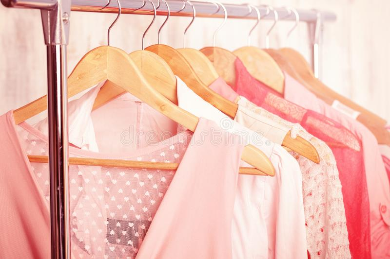 Coral womens clothes on hangers on rack in fashion store. closet stock image