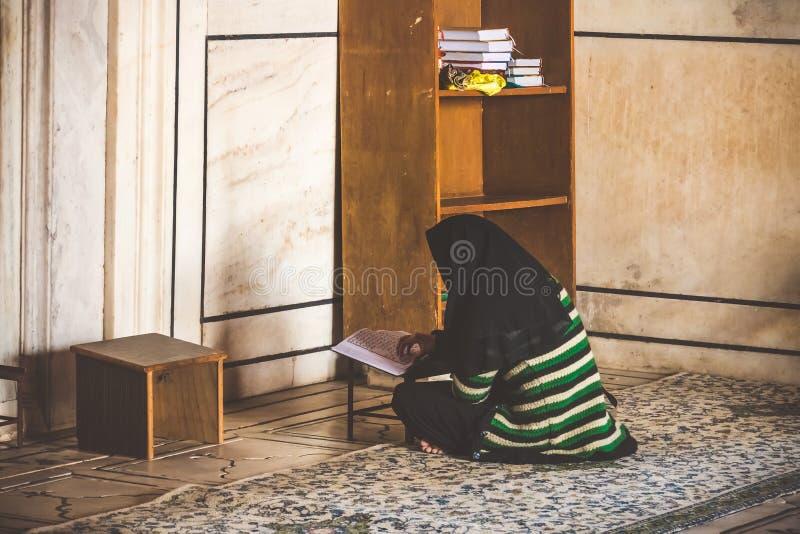 Corano santo leggente della donna musulmana nella moschea indiana Studio di sacra scrittura Una lettura storica dei libri sacri u immagini stock libere da diritti