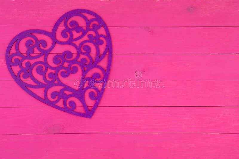 Corazón afiligranado púrpura decorativo en rosa imagen de archivo