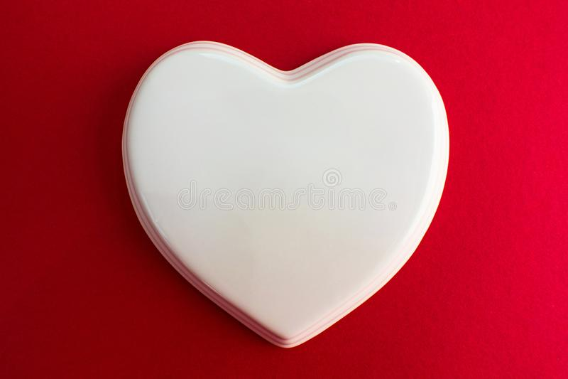 Corazón brillante blanco de la porcelana a un fondo violeta rojo; boda; Invitación de boda; Nota del amor imagenes de archivo