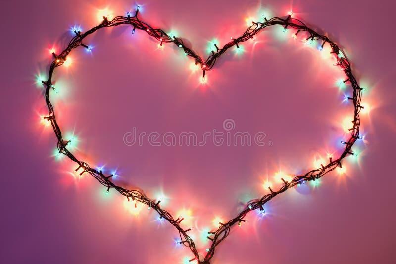 Corazón brillante en fondo rosado oscuro foto de archivo libre de regalías