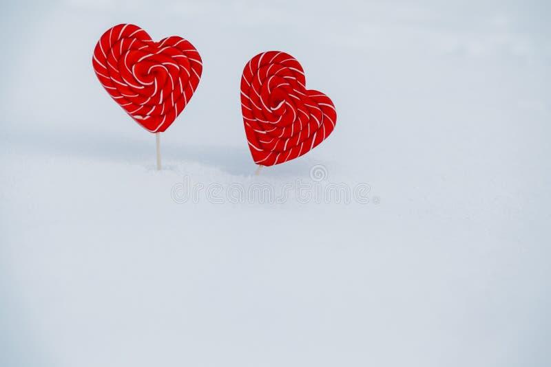 Corazón-caramelo dos en la nieve el concepto de declaración del amor y de los dulces, el día de tarjeta del día de San Valentín U foto de archivo