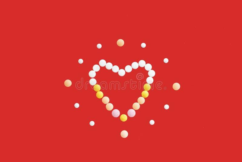 Corazón coloreado de las tabletas y de las píldoras en un fondo rojo fotografía de archivo
