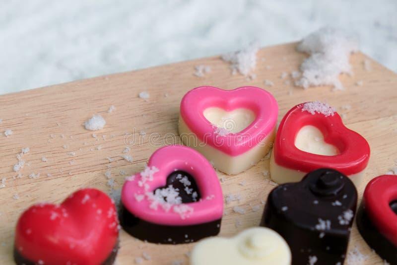 Corazón colorido de los chocolates con leche en la placa y la nieve de madera imagen de archivo libre de regalías