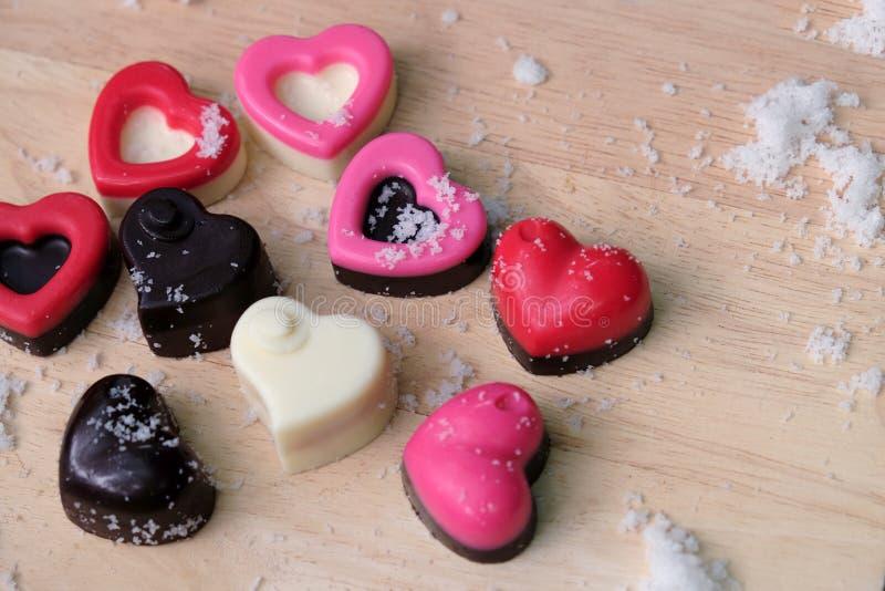 Corazón colorido de los chocolates con leche en la placa y la nieve de madera fotos de archivo libres de regalías