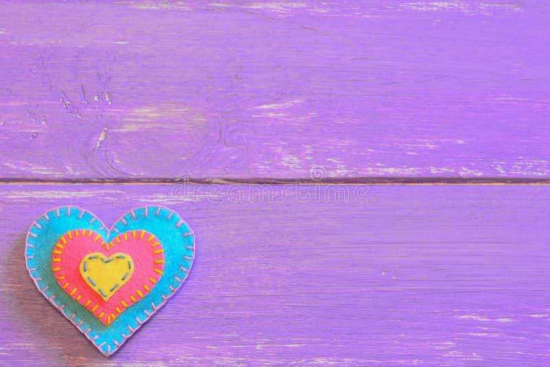 Corazón colorido del fieltro aislado en un fondo de madera púrpura con el lugar vacío para el texto Fondo agradable de la tarjeta imagen de archivo