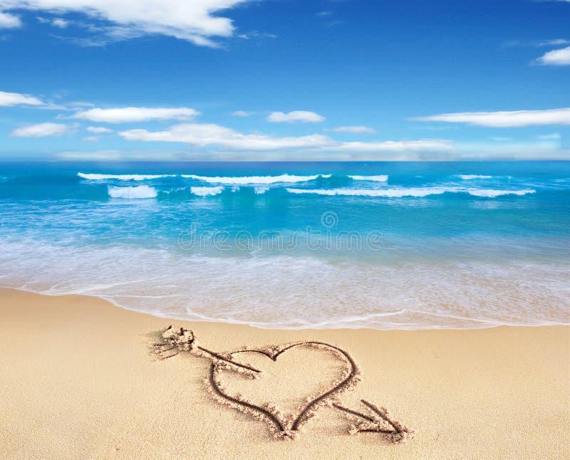 Corazón con la flecha, como muestra del amor, dibujada en la orilla de la playa, con t fotos de archivo libres de regalías