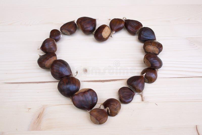 Corazón de castañas marrones en otoño imágenes de archivo libres de regalías