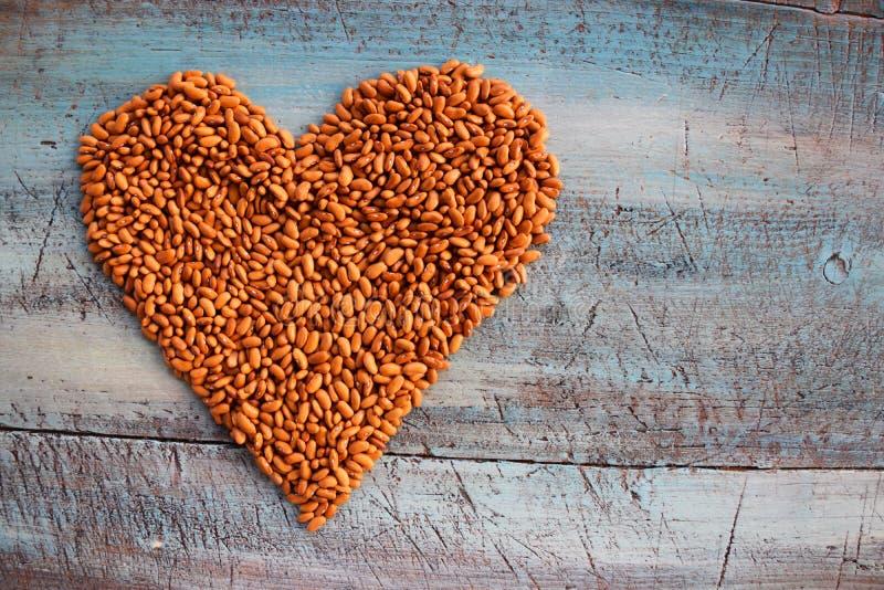 Corazón de habas en el bakground de la tabla imagen de archivo