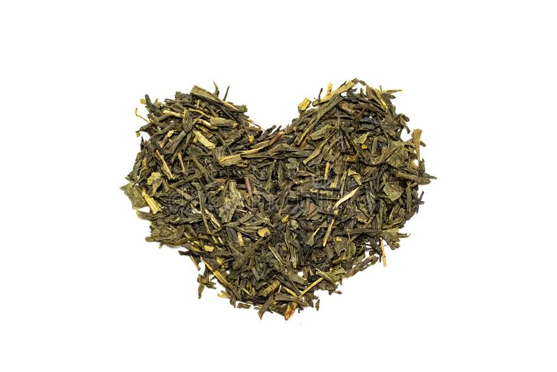 Corazón de hojas de té secadas, aislante en el fondo blanco imagen de archivo libre de regalías