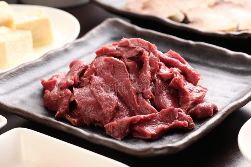 Corazón de la carne de vaca de Silced con el queso de soja en la placa negra en una comida caliente del pote imagenes de archivo
