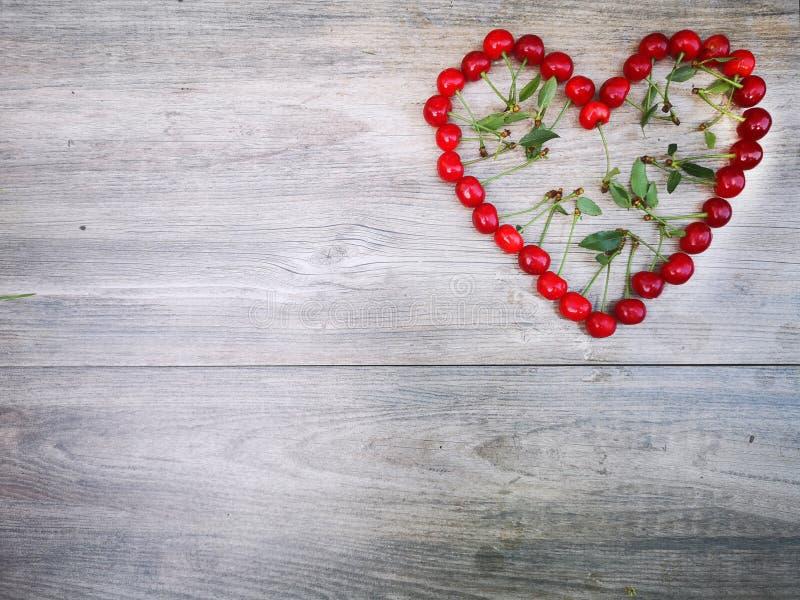 Corazón de la cereza y fondo de madera del modelo fotografía de archivo