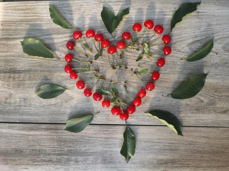 Corazón de la cereza y fondo de madera del modelo imagen de archivo