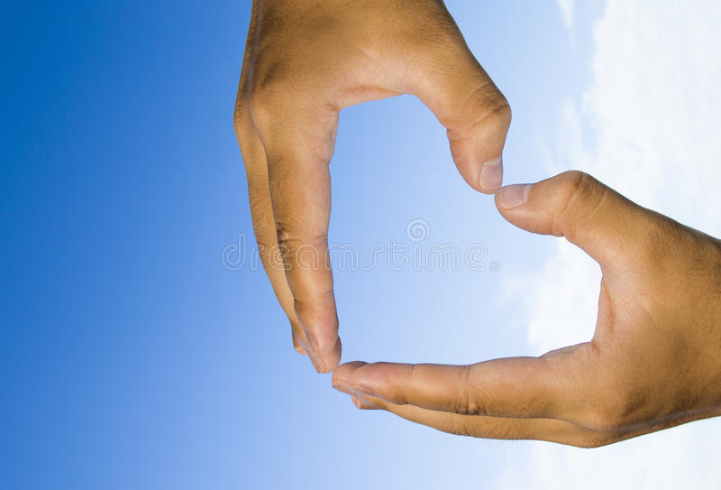 Corazón de la mano en el cielo azul imagen de archivo
