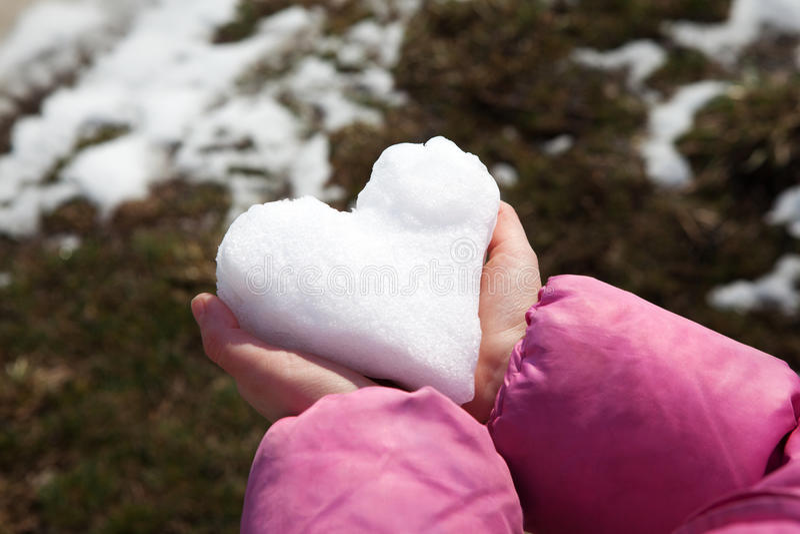 Corazón de la nieve en manos imagen de archivo