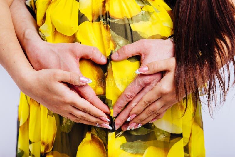 Corazón de las manos dobladas en el vientre de una mujer embarazada imagen de archivo