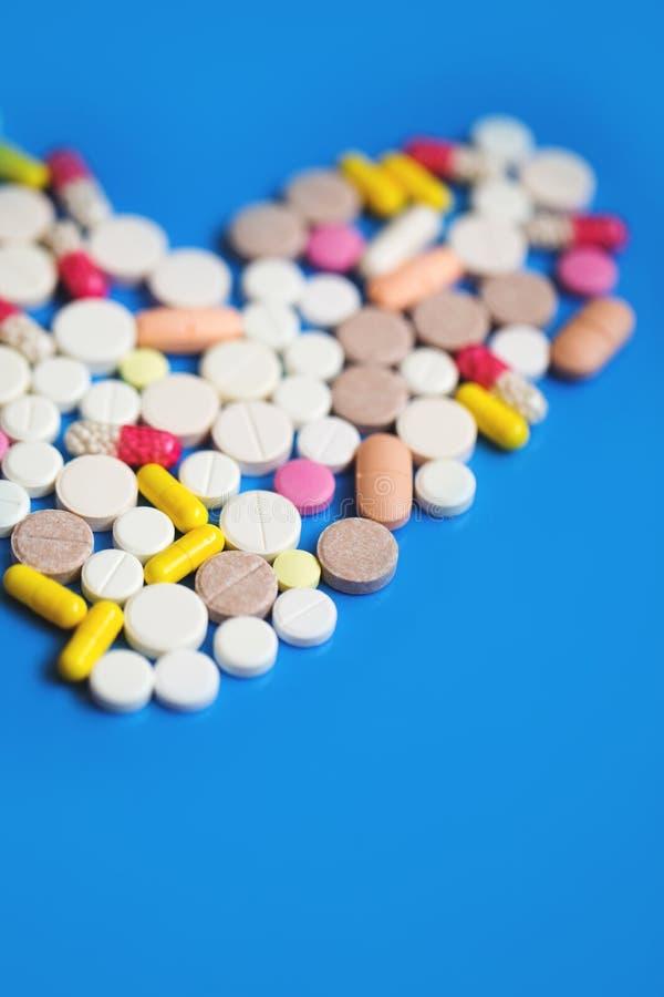 Corazón de las píldoras en un fondo azul fotos de archivo libres de regalías