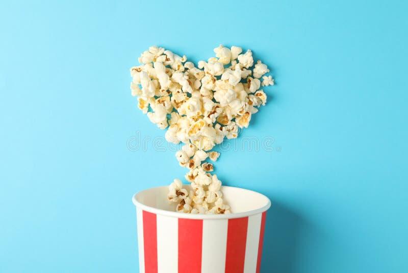 Corazón de las palomitas y cubo rayado en fondo azul foto de archivo libre de regalías