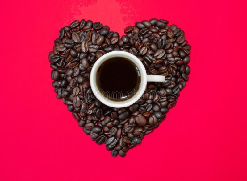 Corazón de los granos de café en un fondo rojo con una taza de café en el centro imagen de archivo libre de regalías