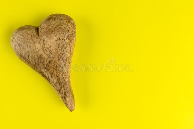 Corazón de madera aislado en fondo amarillo con la trayectoria de recortes y el espacio a la derecha, visión de la copia desde el foto de archivo