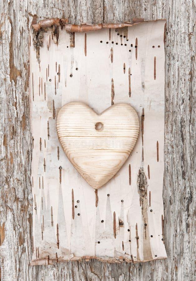 Corazón de madera con la corteza de abedul en la madera vieja imágenes de archivo libres de regalías
