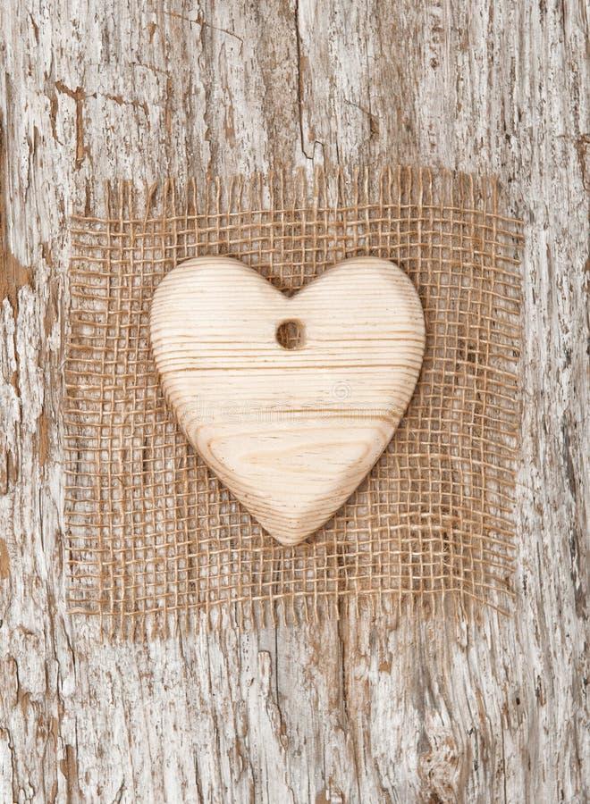 Corazón de madera con la materia textil de la arpillera en la madera vieja imágenes de archivo libres de regalías