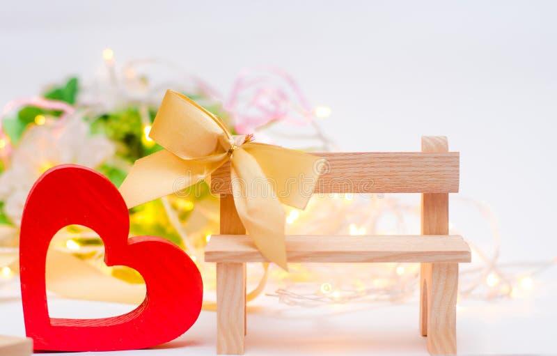 Corazón de madera con un arco en un banco fotografía de archivo