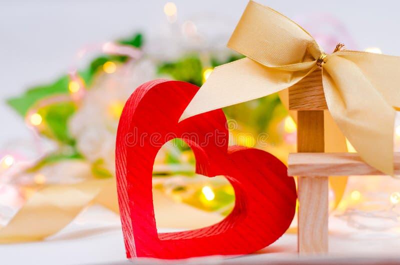 Corazón de madera con un arco en un banco en un fondo blanco Día del `s de la tarjeta del día de San Valentín concepto de amor, d fotografía de archivo