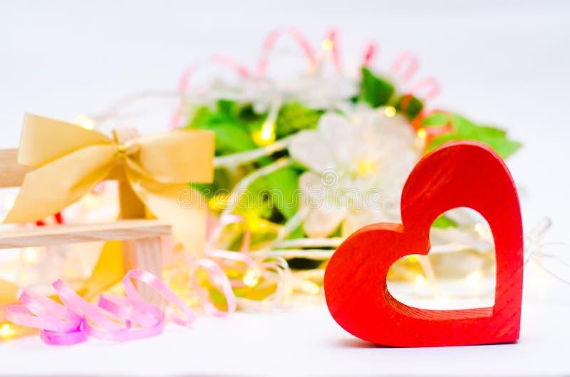 Corazón de madera con un arco en un banco en un fondo blanco Día del ` s de la tarjeta del día de San Valentín el concepto de amo imagen de archivo