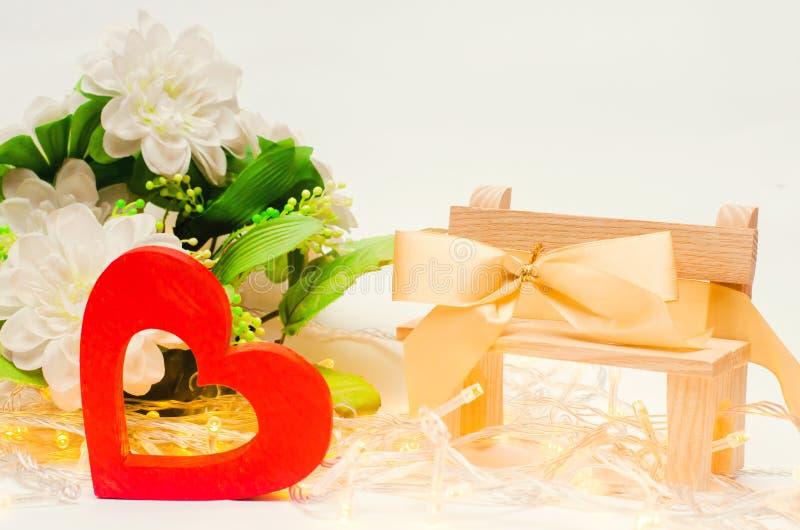Corazón de madera con un arco en un banco en un fondo blanco Día del `s de la tarjeta del día de San Valentín El concepto de amor fotografía de archivo libre de regalías