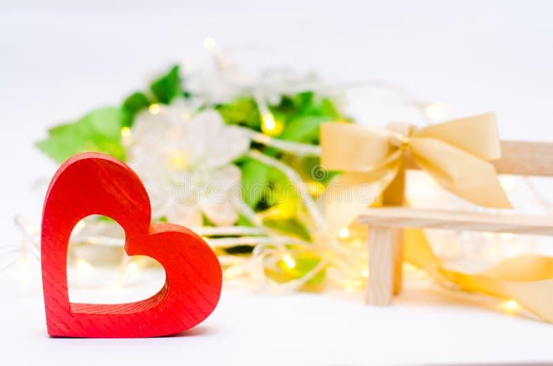 Corazón de madera con un arco en un banco en un fondo blanco Día del `s de la tarjeta del día de San Valentín Presente foto de archivo libre de regalías