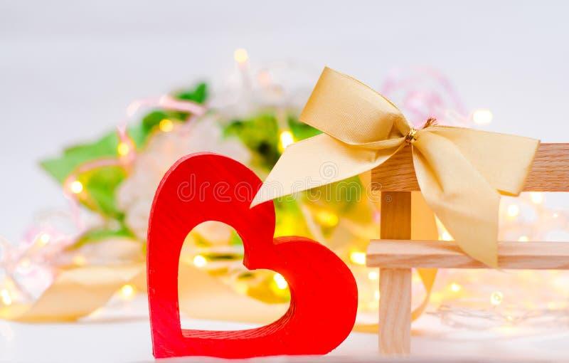 Corazón de madera con un arco en un banco en un fondo blanco Rose roja concepto de amor, decoración romántica imagenes de archivo