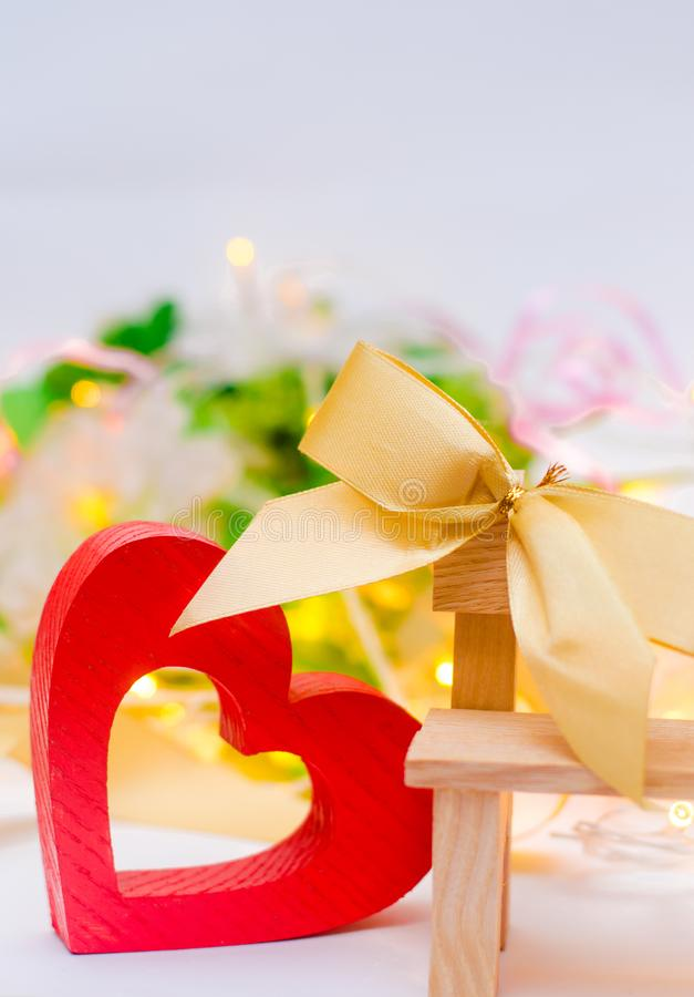 Corazón de madera con un arco en un banco en un fondo blanco Rose roja romance Concepto de amor foto de archivo libre de regalías