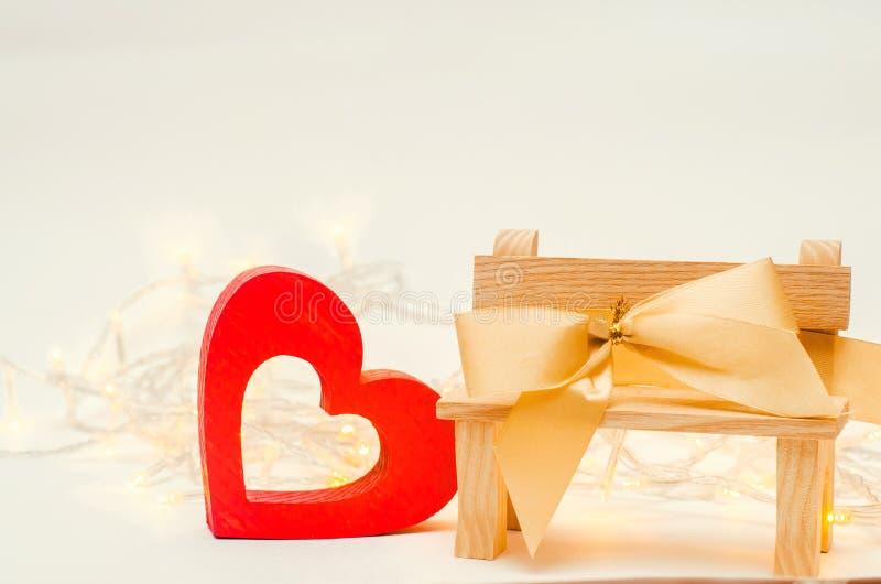 Corazón de madera con un arco en un banco en un fondo blanco Valent imagenes de archivo
