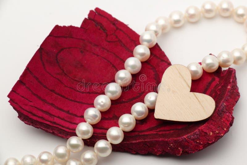 Corazón de madera en caoba de la madera de deriva con las perlas en el fondo fotos de archivo libres de regalías