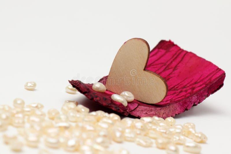 Corazón de madera en caoba de la madera de deriva con las perlas en el fondo imágenes de archivo libres de regalías