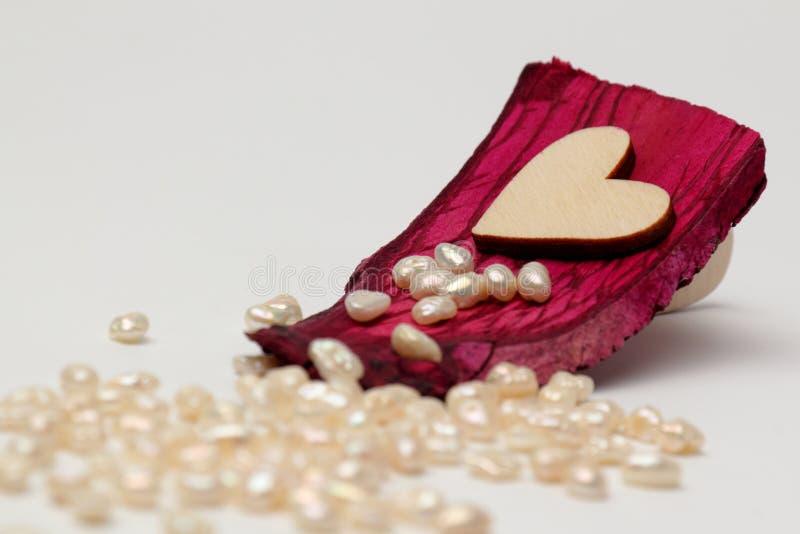 Corazón de madera en caoba de la madera de deriva con las perlas en el fondo foto de archivo libre de regalías
